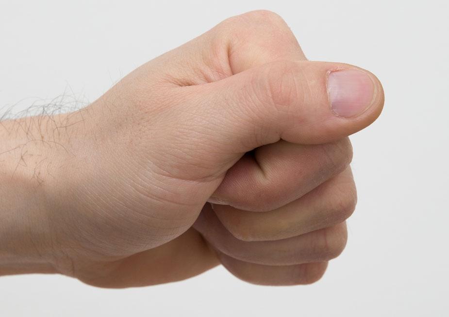 Faust mit Daumen über den Fingern